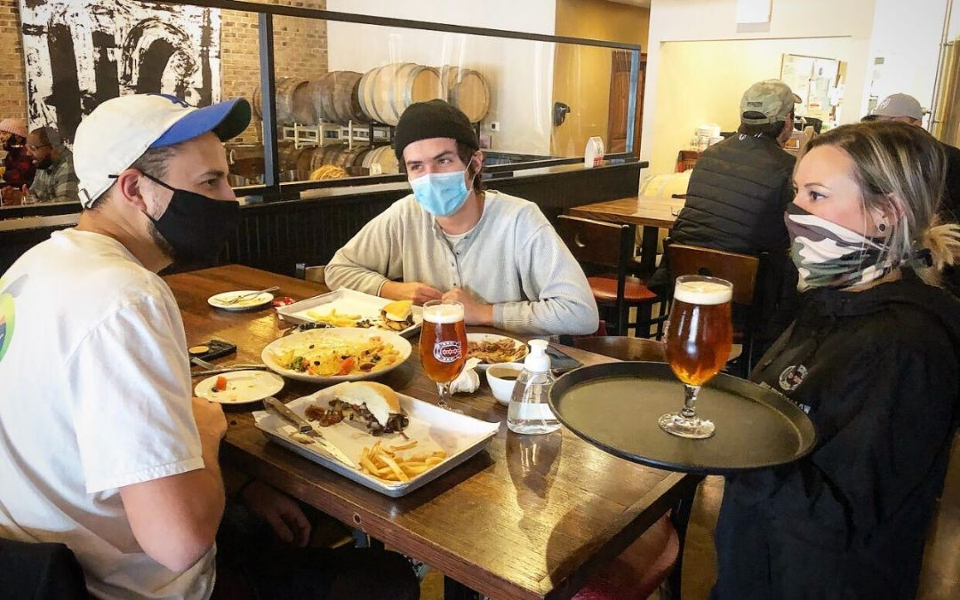 Horse Thief Hollow photo of server and customers wearing masks and using hand sanitizer
