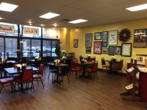 Interior of Calabria Imports showing several small tables and chairs for dining